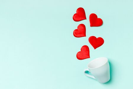 Photo pour Top view of red textile hearts splashing out of a cup on colorful background. Happy Valentine's day concept. - image libre de droit