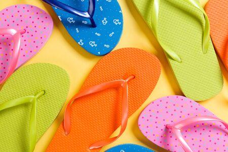 Photo pour many colored flip flops on yellow background. Copy space top view. - image libre de droit