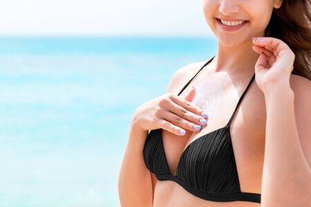 Photo for Young attractive woman is protecting her skin on the breast with sunblock at the sunny beach. - Royalty Free Image