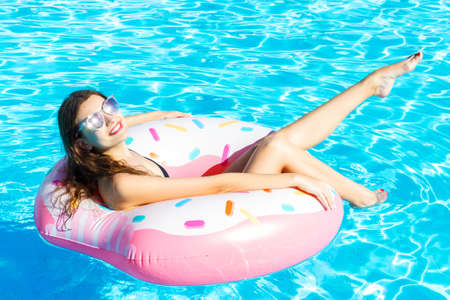Photo pour Young woman in black swimwear is relaxing on donut ring in the swimming pool. Enjoy your summer vacation. - image libre de droit