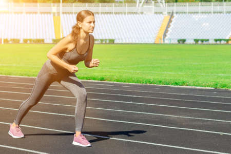 Foto per Young athlete is getting ready to start running on a track. Woman is preparing for competition at the stadium. - Immagine Royalty Free