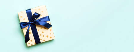 Photo pour Top view woman hands holding Christmas present box with blue bow on blue background with copy space. - image libre de droit
