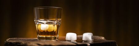 Photo for A glass of alcoholic beverage on a wooden table. Whiskey cocktail with ice - Royalty Free Image