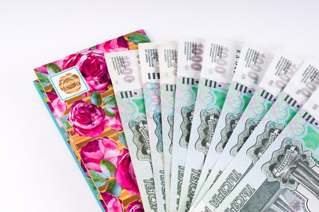 A stack of thousand-ruble banknotes, spread out and an envelope for money. Russian currency on a white background.