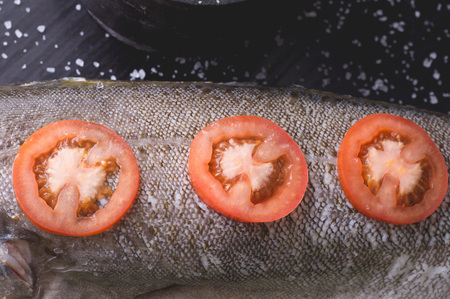 White fish with tomatoes r on a black wooden background. Process of cooking