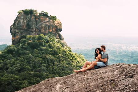 Foto de A couple in love on a rock admires the beautiful views in Sigiriya. - Imagen libre de derechos