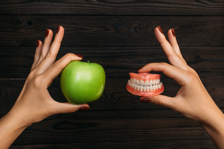 Foto de False teeth denture against green granny smith apple. Dental prosthesis care. Denture and Apple in the hands of a doctor. Dental care. Beautiful tooth. Prosthetics. False teeth - Imagen libre de derechos