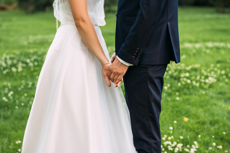 Foto für Hands of bride and groom. New young couple holding hands after their wedding. Young married couple holding hands, ceremony wedding day. Closeup view of married couple holding hands - Lizenzfreies Bild