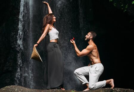 Photo pour A man proposes to a woman at a waterfall. A guy proposes to a girl in Bali. Offer of a hand in travel. Honeymoon trip. Declaration of love. A couple in love on a waterfall. Happy couple in bali - image libre de droit