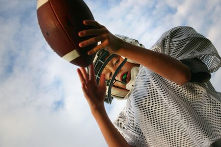 A teenager holding a football ready to kick it