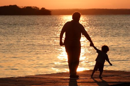 An adult and a child walk out on a dock as the sun sets