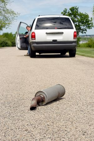 A man is getting out of his car and looks back to see his car's muffler laying on the ground