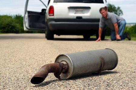 A man kneals on the ground by his car and looks back to see his car's muffler laying on the ground