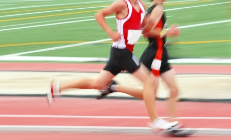 a motion blur of two runners on a red track