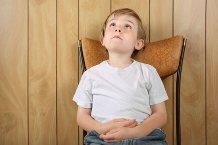 Photo for a young boy sits in a chair while waiting for something to happen - Royalty Free Image