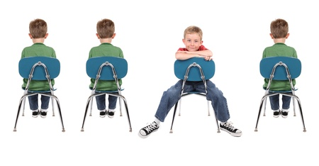Photo pour A group of boys sit in school chairs. One is facing backwards and is wearing different clothes than the other boys. - image libre de droit