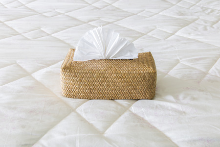 Tissues in bamboo box on the bed