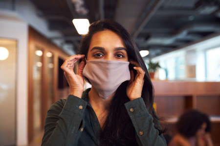 Photo for Portrait Of Businesswoman Wearing Face Mask In Modern Open Plan Office During Covid-19 Pandemic - Royalty Free Image