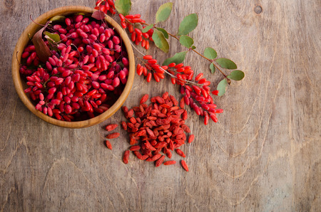 Barberry in bowl with leaves and dry goji berries on wooden background