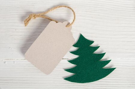 Christmas tag with fabric christmas tree on wooden background