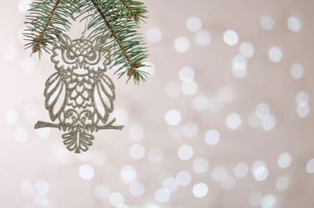 Photo pour A white toy owl hangs on a Christmas tree branch. Bokeh. Christmas decoration - image libre de droit