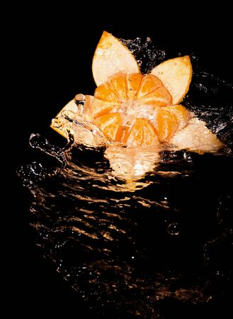 Mandarin peel in the form of a flower and mandarin segments in a stream of water on a black background
