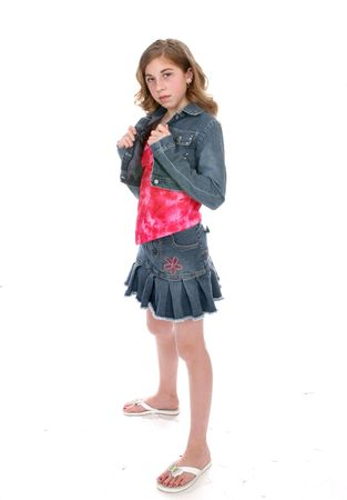 Defiant looking young girl wearing a short denim mini skirt and a cropped denim jacket.
