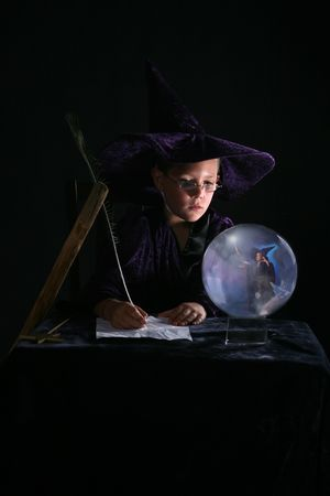 child in wizard costume writing a spell and gazing into crystal ball