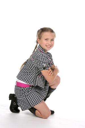 fashionable girl kneeling and smiling with arms crossed