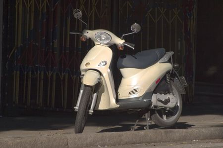 A small motor scooter is parked on the sidewalk.