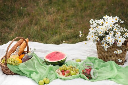 Summer picnic in the meadow on the green grass. Fruit basket, juice and bottled wine, watermelon and bread baguettes. White tablecloth and a bouquet of field daisies. The concept of recreation and food in nature.
