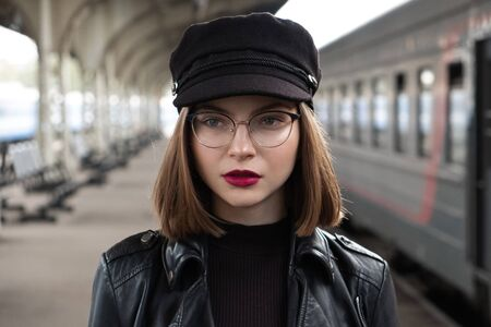 Attractive young woman millenial in black clothes and a hat and glasses at the railway station next to the train. Serious look, waiting for the train. Big clock on the background.