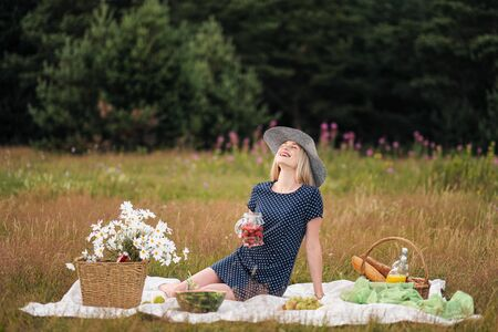 Young attractive woman in a blue dress at an outdoor picnic. A basket with daisies, watermelon, strawberries and a glass of lemonade. The concept of summer outdoor recreation.