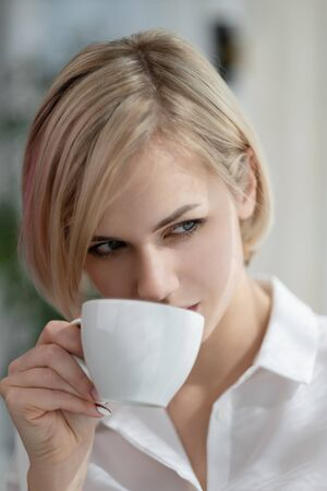 Photo for Young beautiful blonde woman in white shirt and glasses is sitting on the sofa in bright office against the window. Holds a white cup and drinking coffee or tea in a working break. Relaxation concept. - Royalty Free Image