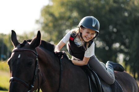 Photo for Girl teenager jockey sits on a brown horse in nature. Dressage horses, rider training. - Royalty Free Image