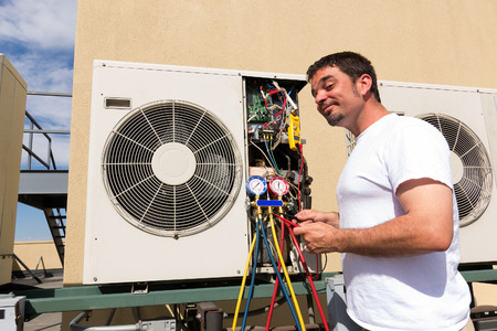 HVAC technician working on a mini-split condensing rooftop unit