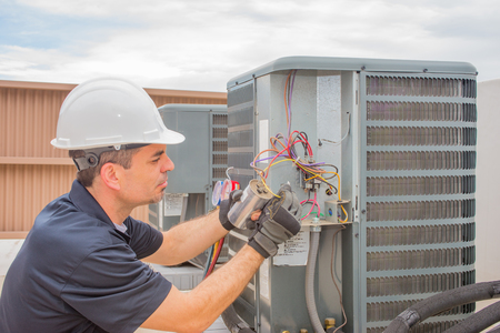 Photo for HVAC Technician checking capacitor on air conditioner - Royalty Free Image