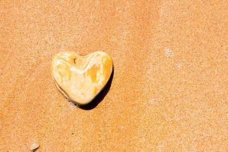 Photo pour A heart-shaped stone lies on the sand as a symbol of love. - image libre de droit
