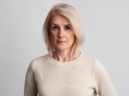 sad beautiful aged woman wearing sweater over grey studio wall.