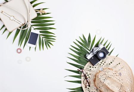 5353c183 Traveler feminine accessories and tropical palm leaves with empty space for  text on white background.