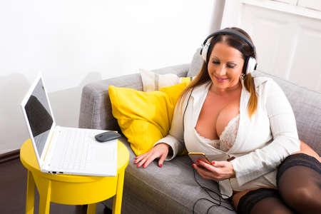 Foto de A big and beautiful woman relaxing in lingerie on the Sofa. - Imagen libre de derechos