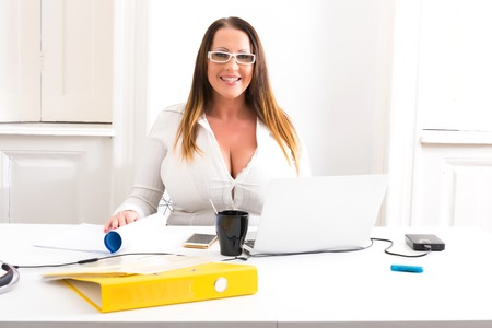 Foto de Big and Beautiful Secretary working in a office - Imagen libre de derechos