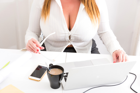 Photo for A plus size big and beautiful and voluptuous Secretary working at the Desktop with a Laptop. - Royalty Free Image