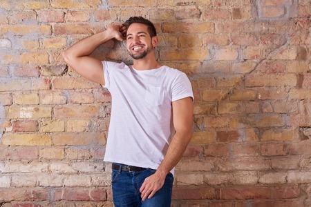 Foto de Portrait of a happy handsome young man in a white tshirt. - Imagen libre de derechos
