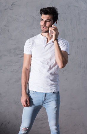Photo for A happy handsome young man in a white tshirt talking on his phone in front of a grey wall in a studio. - Royalty Free Image