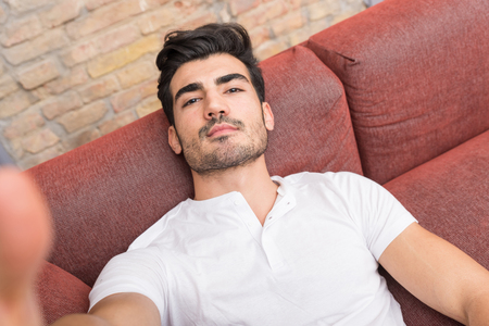 Photo for Portrait of a serious handsome young man talking a selfie while sitting on a sofa in a white tshirt from the perspective of the smartphone. - Royalty Free Image
