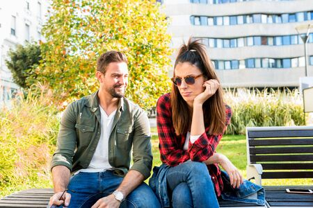 Photo for A girlfriend being annoyed by her boyfriend on a sunny day on a park bench.. - Royalty Free Image