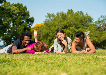 Photo pour A group of friends laying together in the lawn in a park on a sunny summer day. - image libre de droit