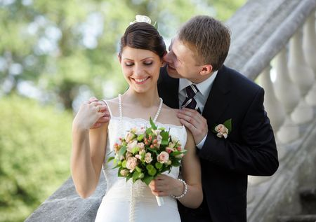 Portrait of a bride in a beautiful white traditional wedding dress. Her new husband is whispering in her ear,