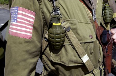 Details of American World War two GI soldier wearing army uniform with hand grenades and pistol.